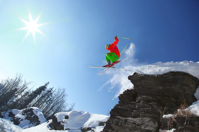 skier jumping off rock