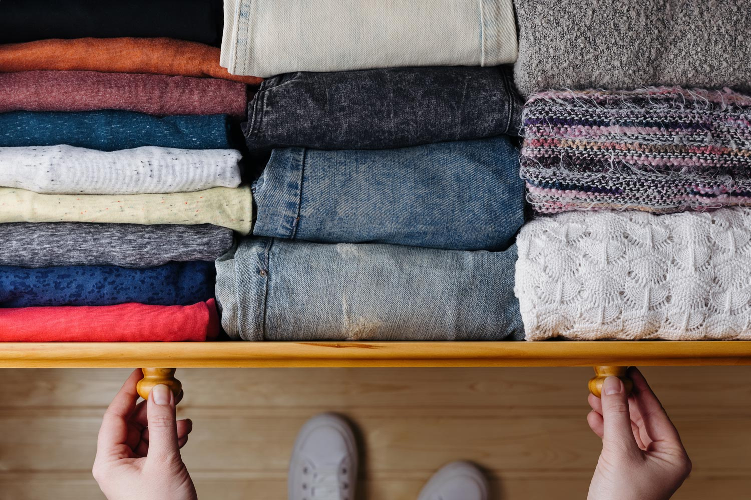 pushing clothes into a drawer